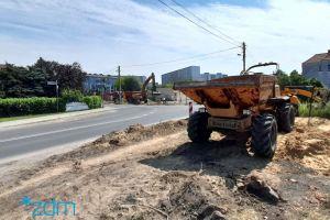 Po lewej stronie jezdnia ulicy, na prawo plac budowy na którym stoją pojazdy budowalane