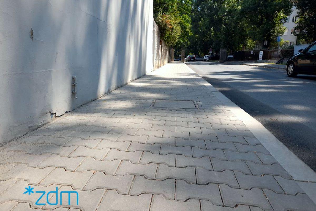 Chodnik na ulicy Sielawy. Po lewej stronie mur, obok chodnik z płytek betonowych. Po prawej stronie jezdnia