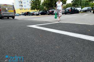 Wyremontowany chodnik. Obok jezdnia przez którą przechodzi kobieta