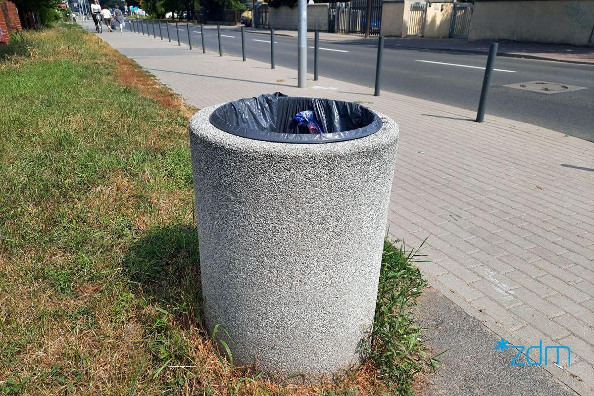 Betonowy kosz na śmieci stojacy przy chodniku