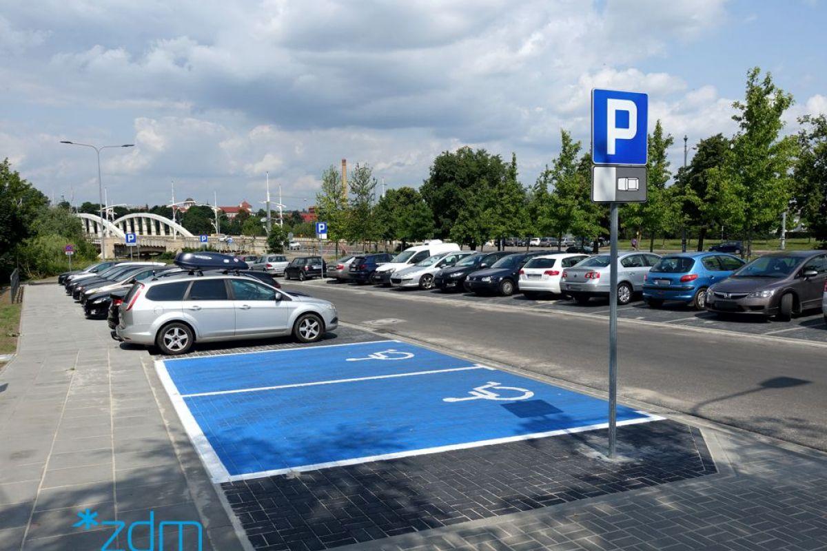 Po lewej stronie chodnik, na prawo od niego dwie puste koperty dla pojazdów osób z niepełnosprawnością. Ulica i parkujące samochody