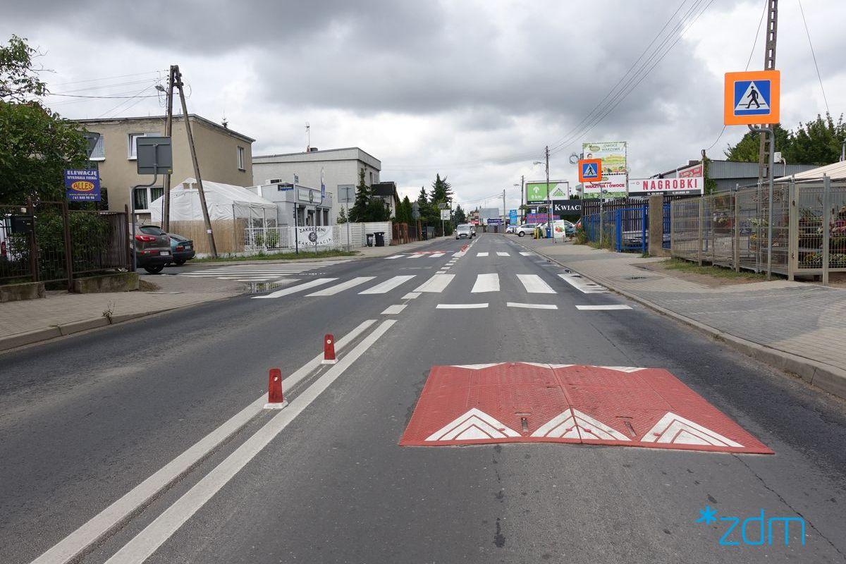 Ulica Malwowa w Poznaniu. Na jezdni poduszki spowalniające prędkość samochodów. Za nimi przejście dla pieszych i znaki o przejściu