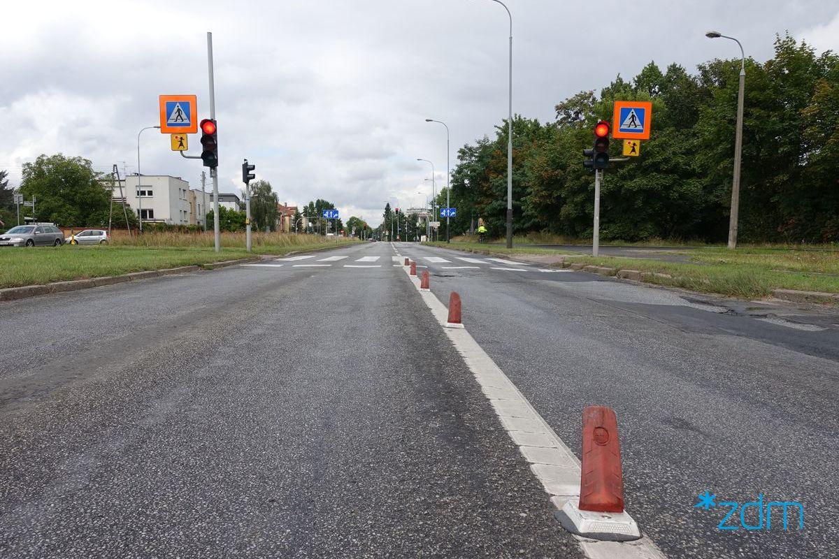 Ulica Grochowska. Dwie jezdnie. Pomiędzy nimi tzw. płetwy mające zawęzić jezdnię. Za nimi przejście dla pieszych i znaki na pomarańczowym tle