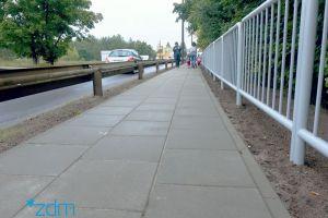 Po środku nowy chodnik. Po jego prawej stronie baierli oddzialające od jezdni ulicy, a po prawej od skarpy