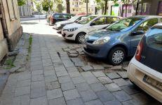 Zniszczony chodnik i parkujące samochody