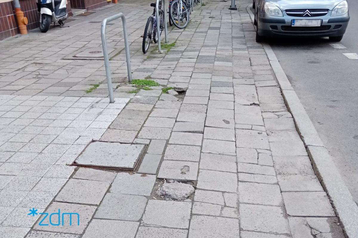 Zniszczony chodnik, w tle parkujący samochód