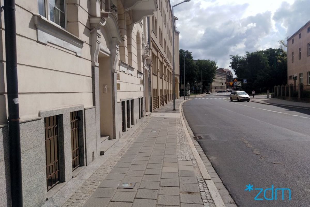 Po lewej stronie odnowiona kamienica. Po środku pas z chodnikiem ptrzeznaczonym do remonty. Na prawo jezdnia ulicy. W tle drzewa
