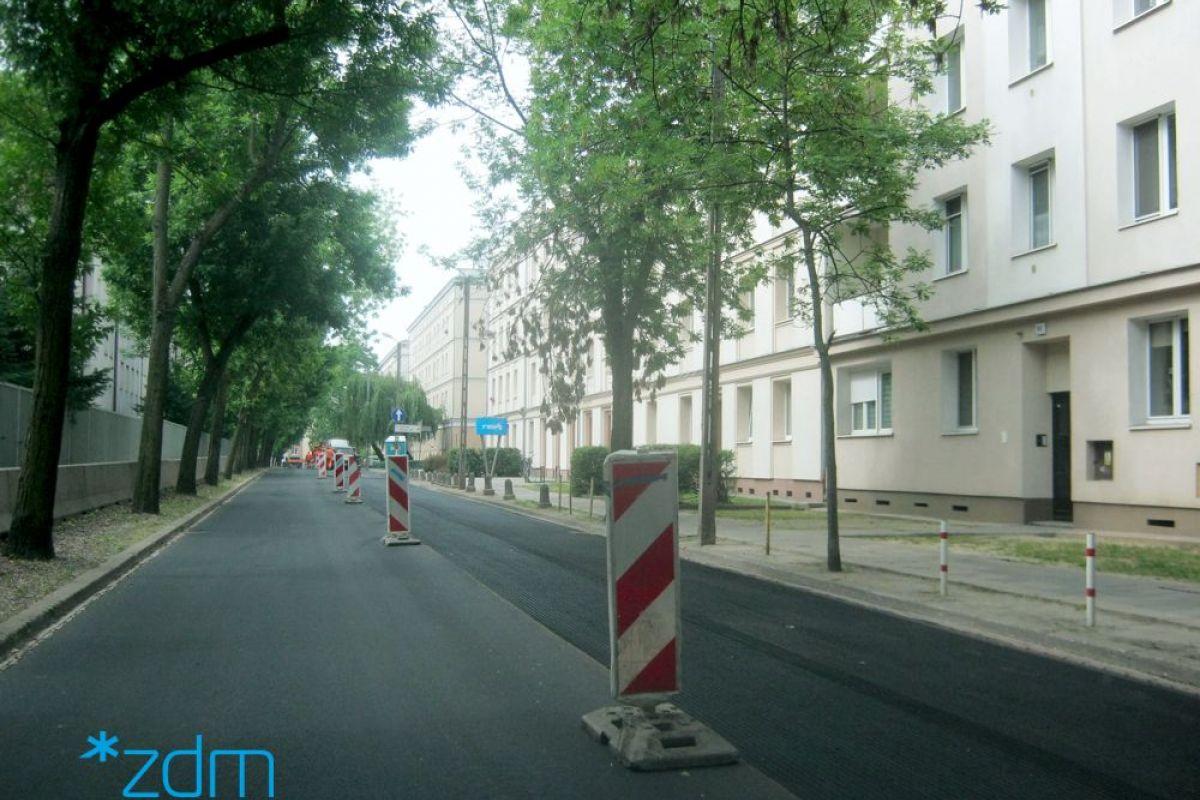 Wyremontowana nawierzchnia jezdni. Po środku ulicy pachołki drogowe. Po bokach drzewa