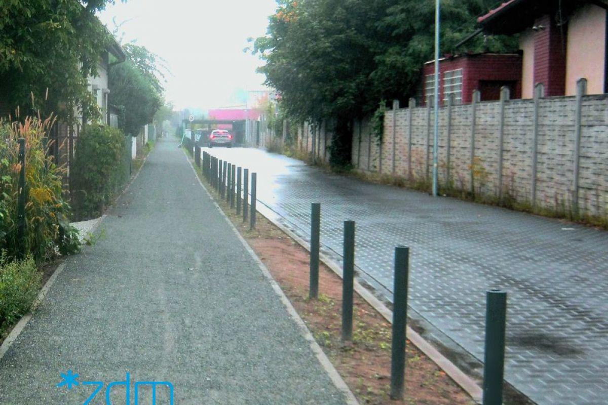 Po lewej stronie nowy chodnik. Na prawo od niego ulica i płot
