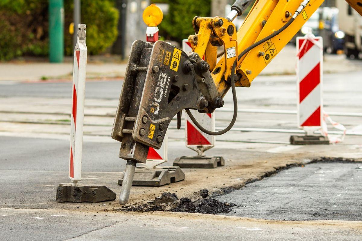Po lewej stronie pachołek drogowy, po środku maszyna zrywająca asfalt. Po prawej jezdnia z zerwaną częścią nawierzchni