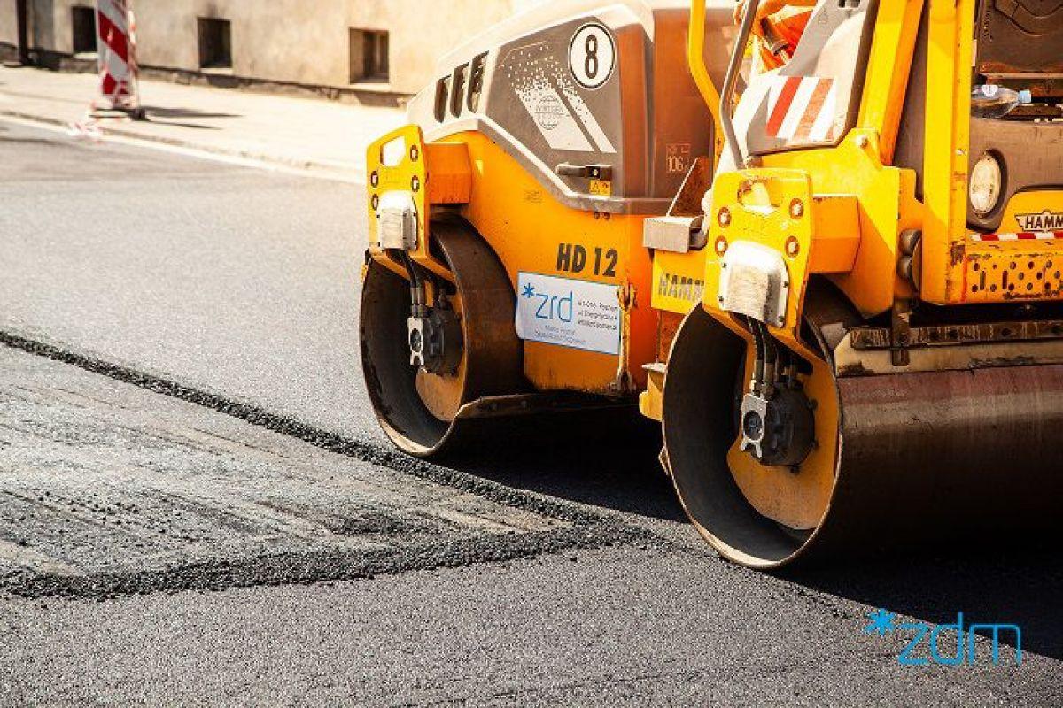 Układanie asfaltu. Po lewej stronie robotnik, a obok wartwa spodnia, po prawej walec na ułożonej warstwie wierzchniej