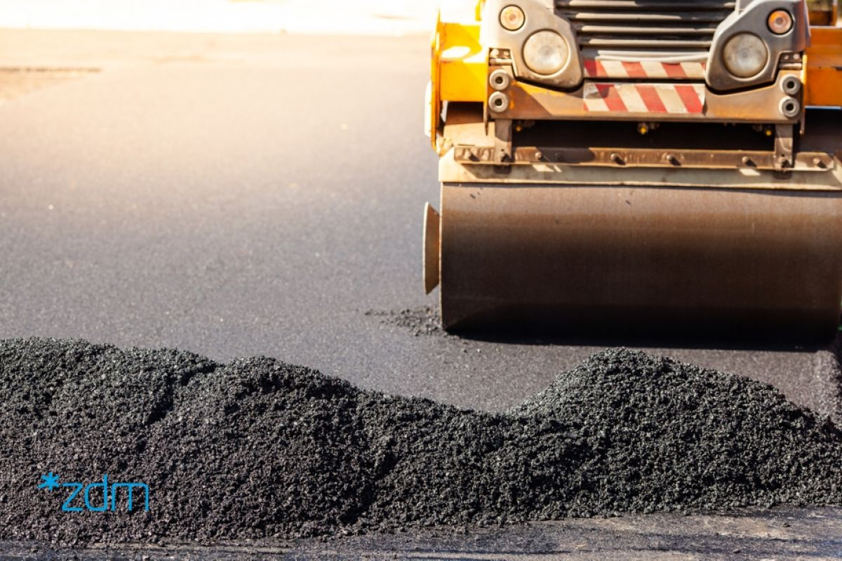 Mała górka asfaltu wysypanego na jezdnię. Za nim żółta maszyna drogwców