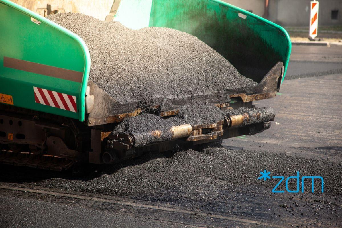 Maszyna drogowa po lewej stronie, po prawej wylany asfalt