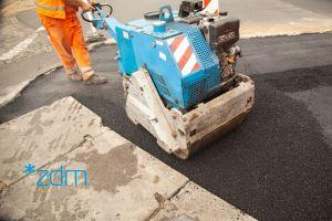 Robotnik w pomarańczonym kombinezonie prowadzi maszynę do wyrównywania asfaltu