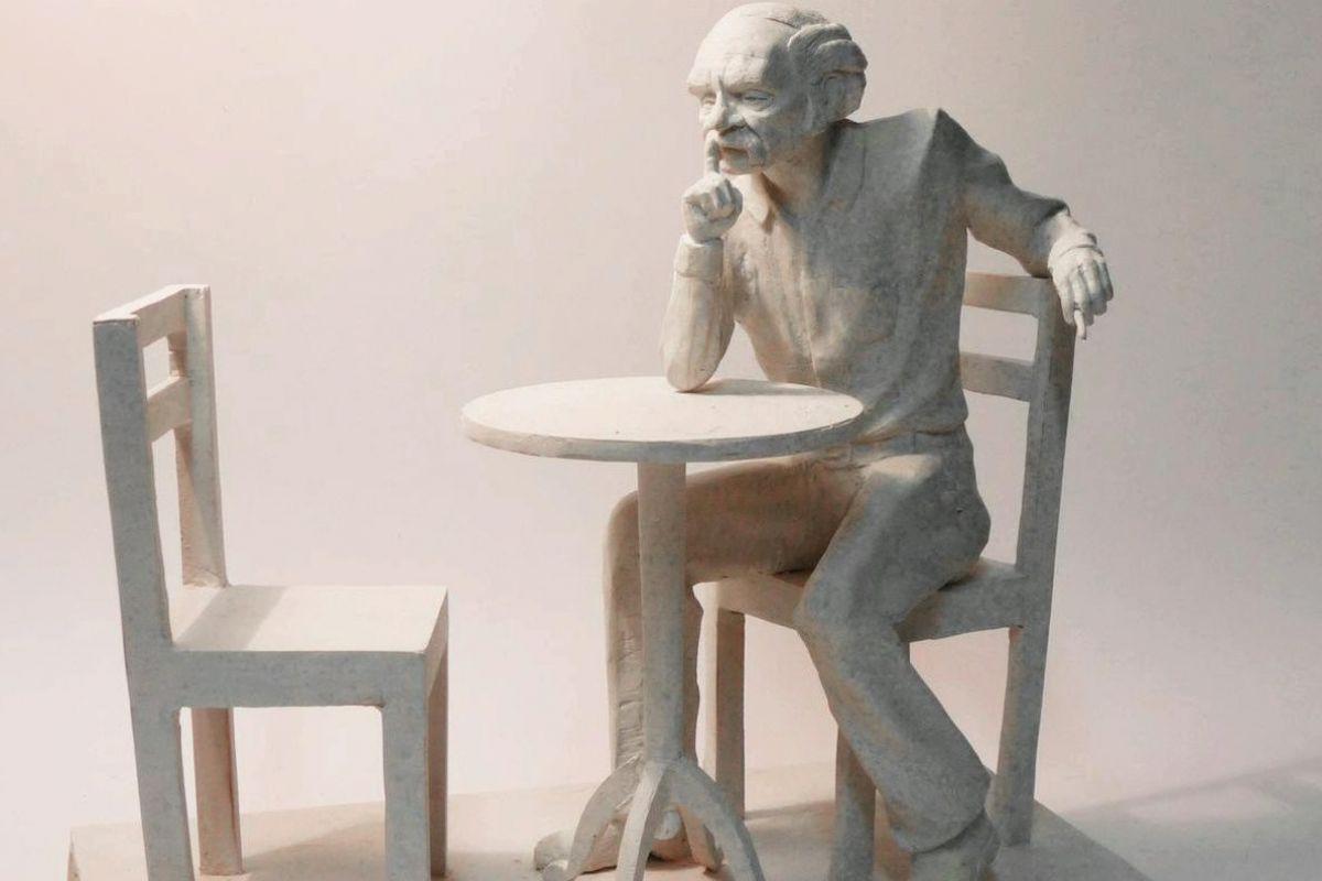 Makieta pomnika Smolenia. Po lewej stronie puste krzesło, na środku stół o który oparty siedzi na krześle po prawej stronie Bohdan Smoleń
