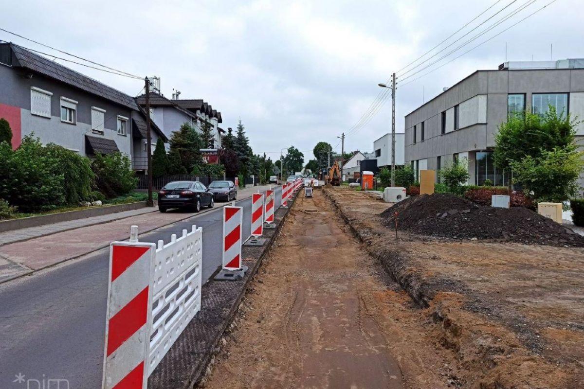 Po prawej stronie domki jednorodznne. Na prawo od nich chodnik i jezdnia. Po lewej stronie wykop w którym będzie droga dla rowerów