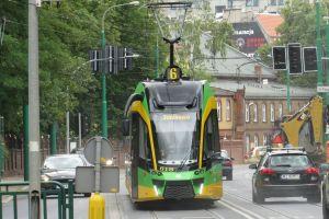 Tramwaj na poznańskiej ulicy. Po prawej stronie jadące samochody