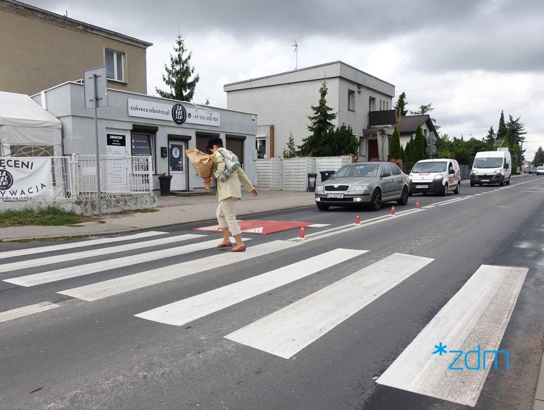 Przejście dla pieszych na ul. Malowej. Na pasach idzie kobieta. Na jezdni próg spowalniający a za nim samochody