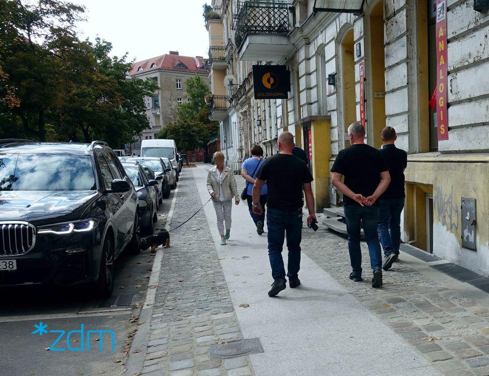 Grupka osób spacerujących po wyremontowanym chodniku. Moja ich pani wyprowadzająca psa na spacer